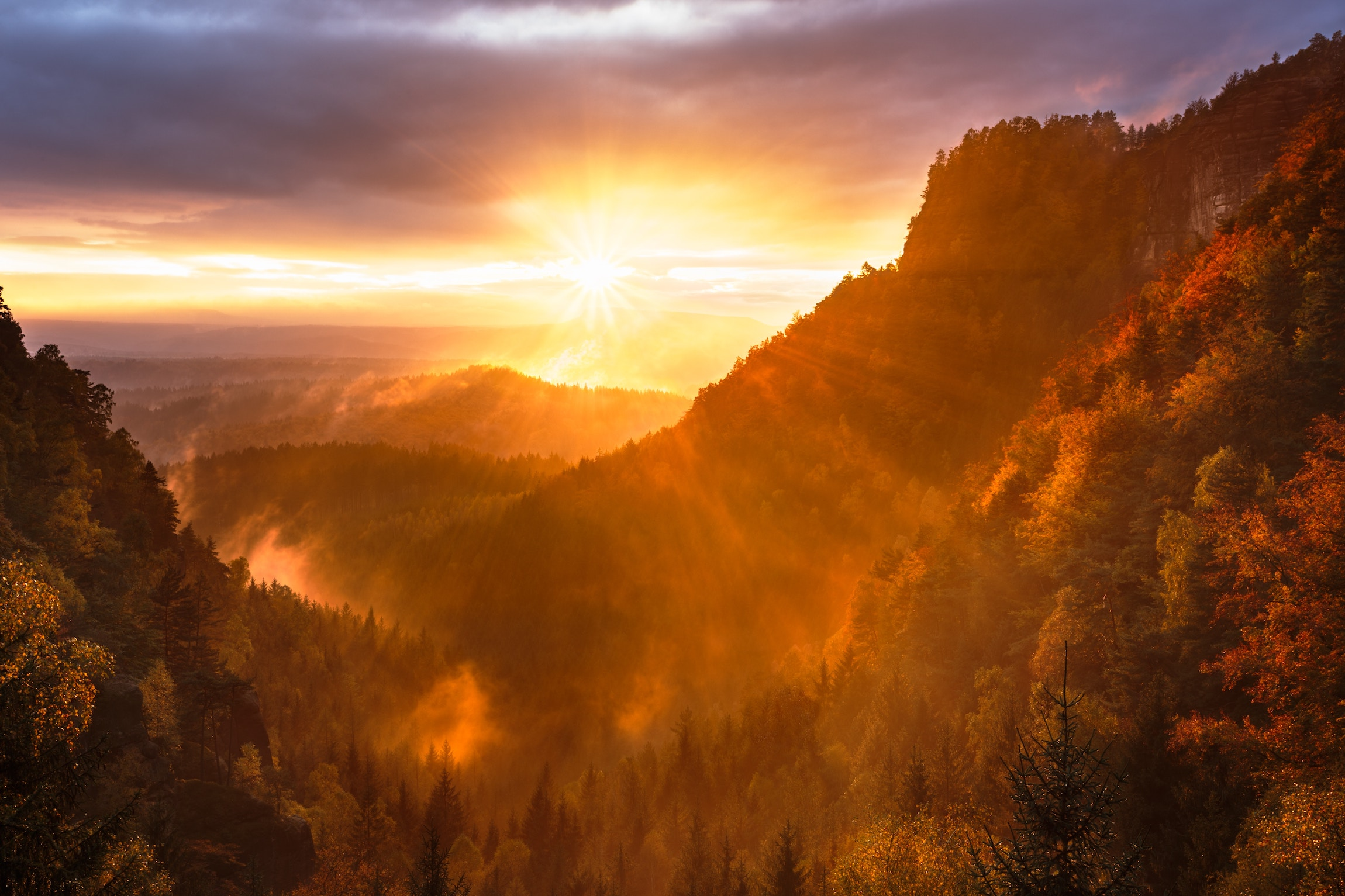 Orange sun with rays spread over a valley created by mountains