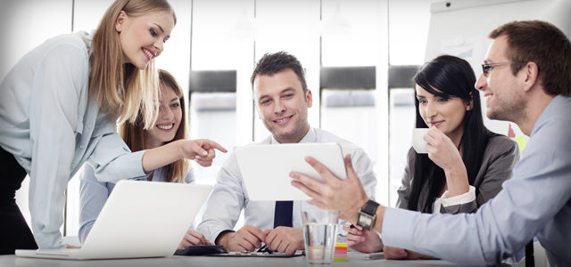 Group of co-workers smiling and laughing together while looking at a tablet