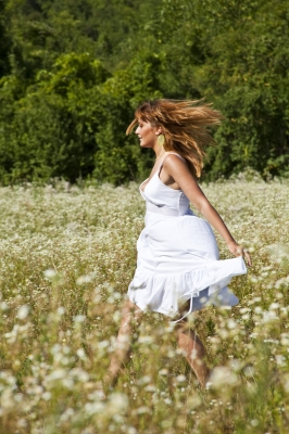 Woman in white dress walking through a field of wildflowers with the wind blowing