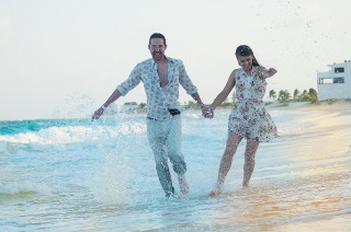 Man and woman holding hands splashing water with their feet while walking down the beach
