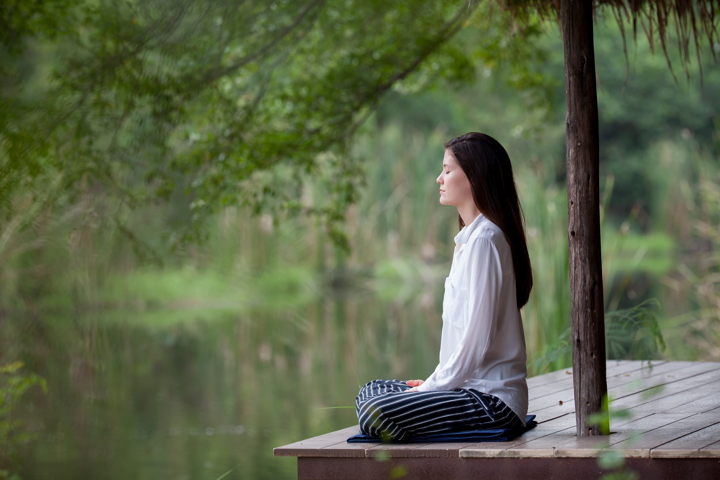 Long-haired woman meditating on the dock of a lake.