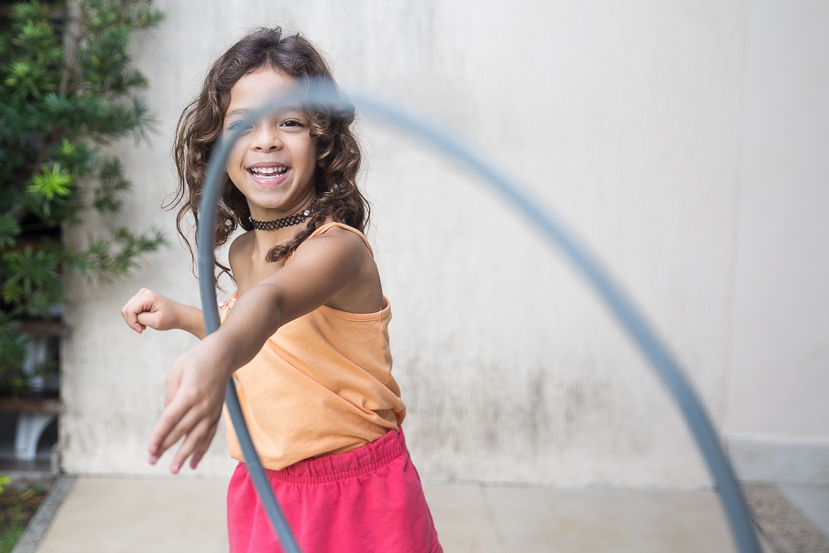Girl in peach tank top and pink shorts tossing a hula hoop toward the camera.