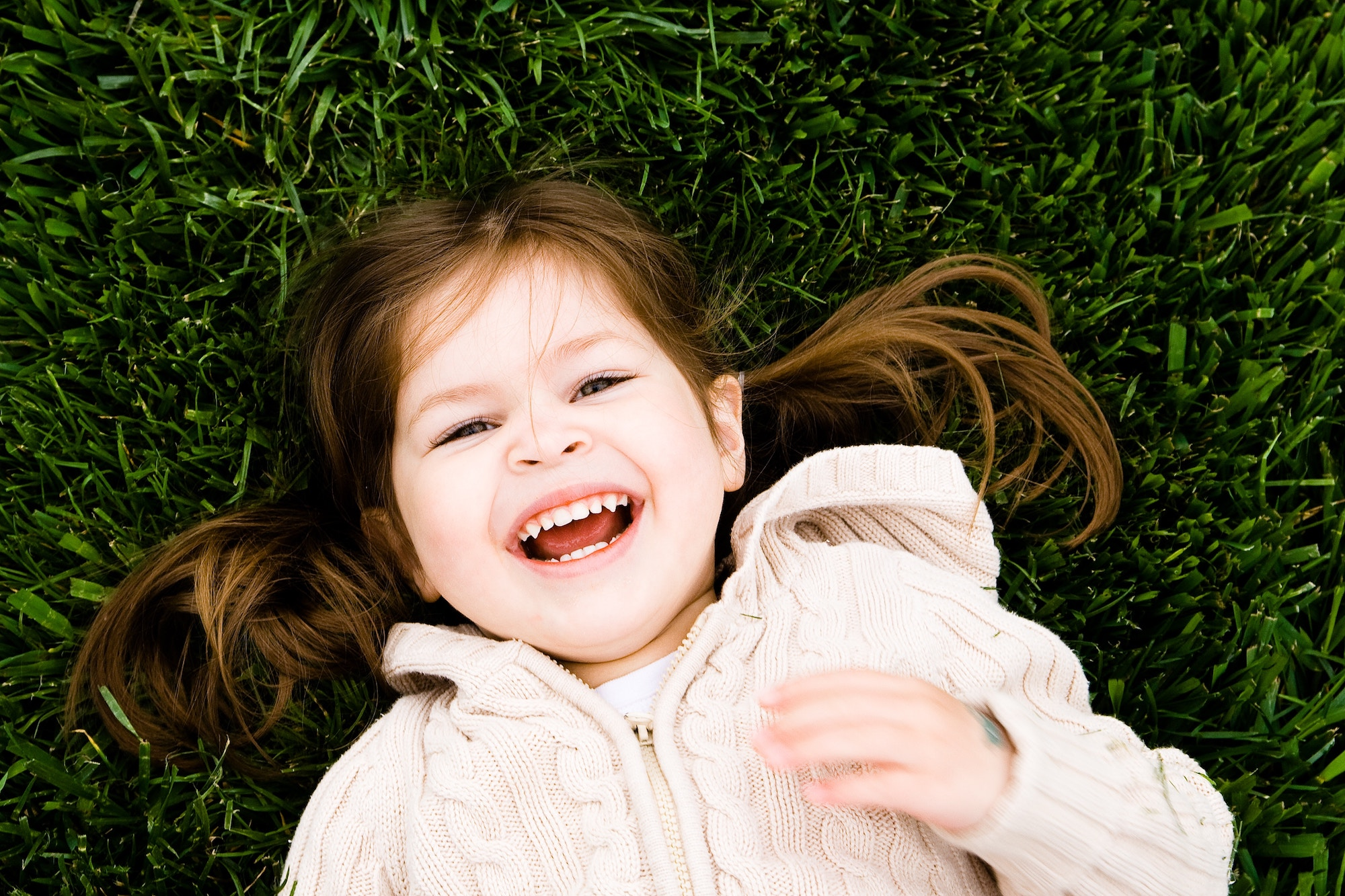 Little girl laying on grass in a pink jacket, smiling as the camera captures her from above.