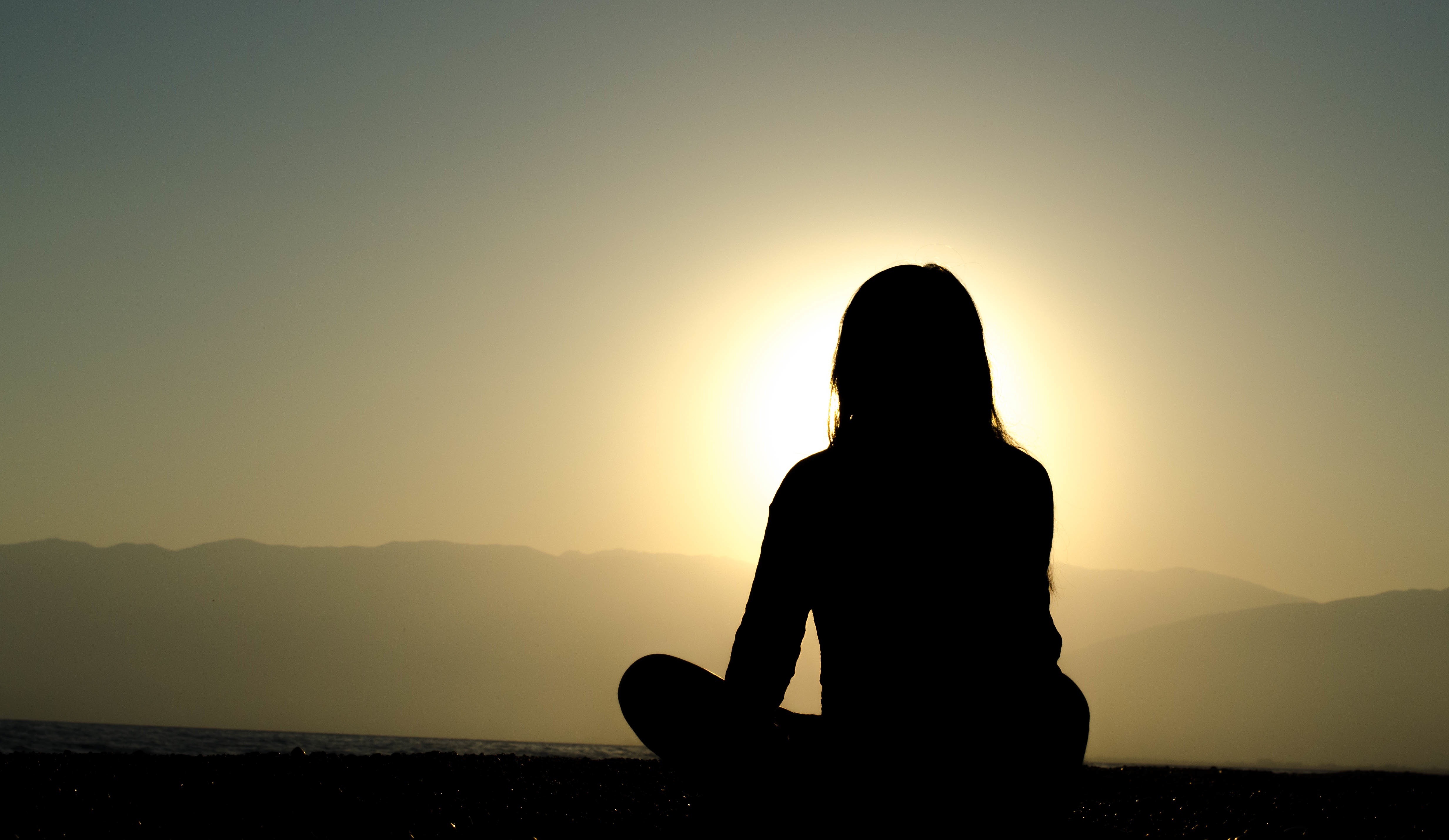 Silhouette of a woman meditating outside under the sunset