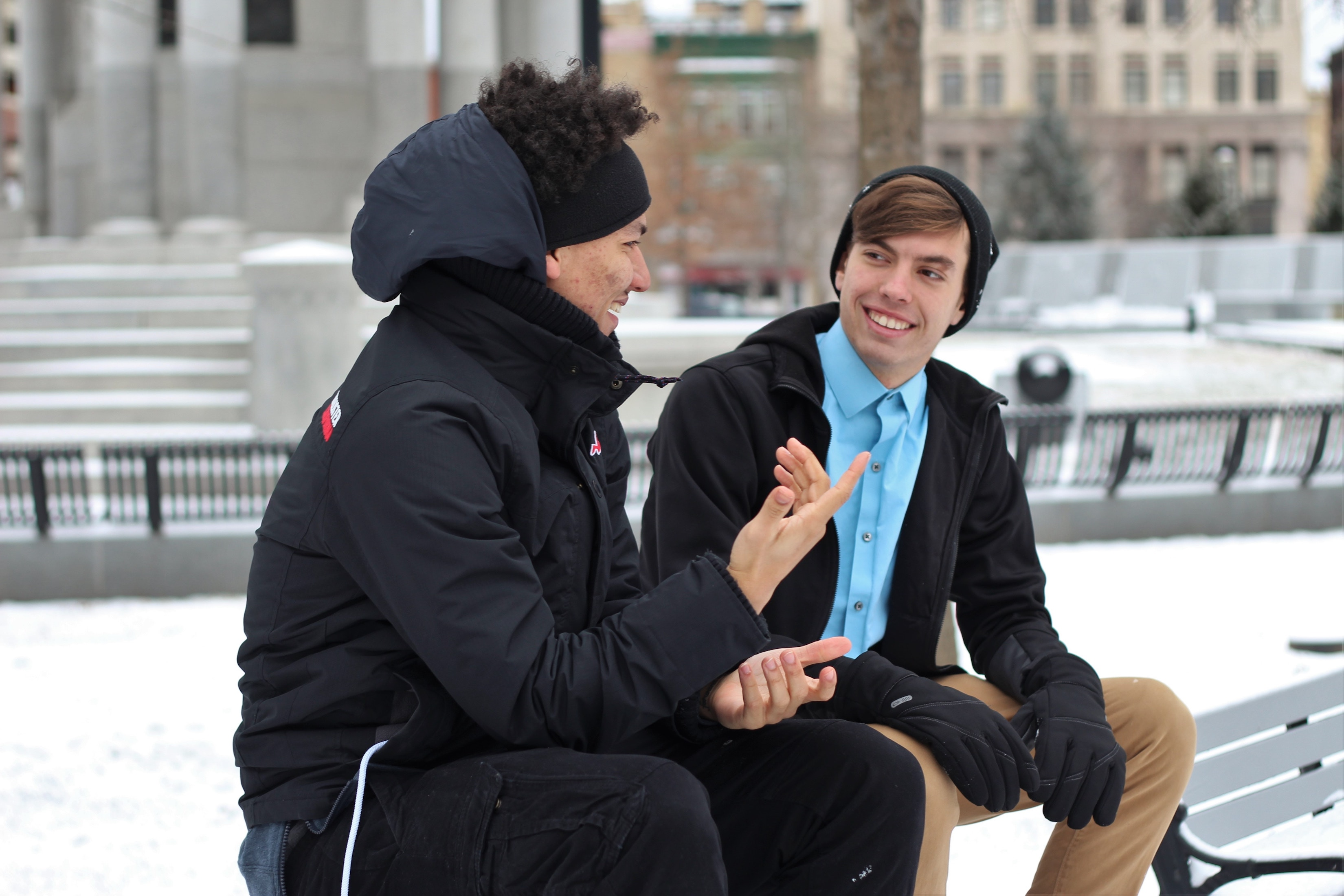 Two guys sitting on a park bench in the snow having a conversation.