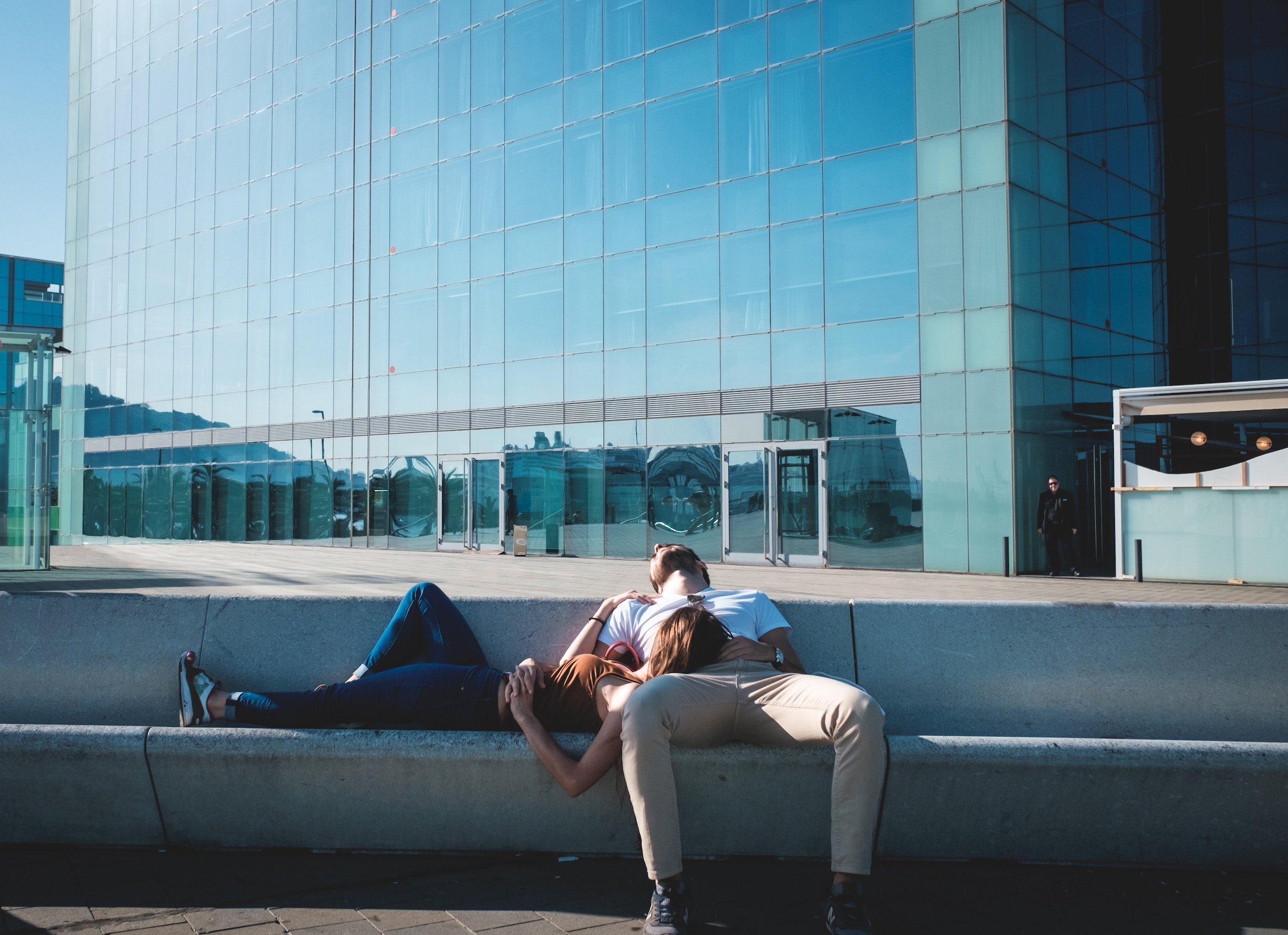 Man lying back on a concrete bench, his spouse laying horizontally with her head on his leg.