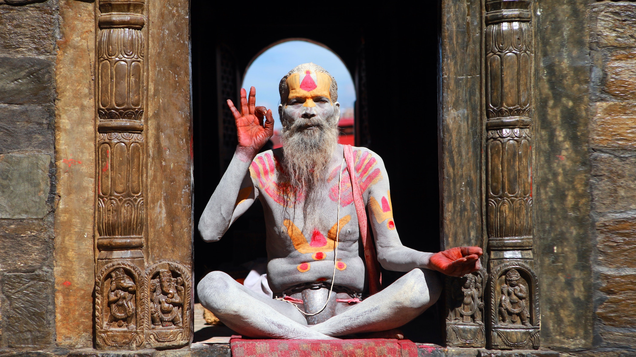 Man covered in body paint meditating in the sun, the fingers on his right hand forming an