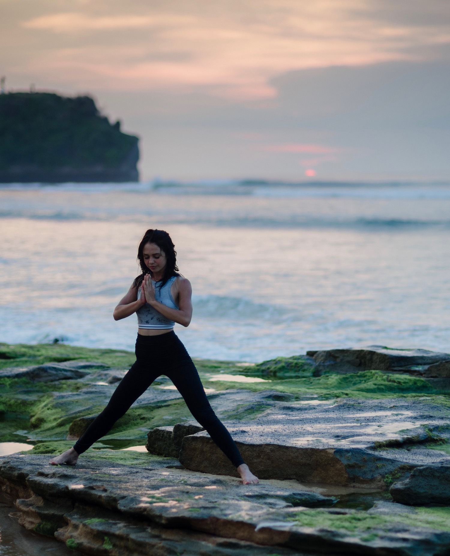 Barefooted woman on rocks surrounded by water doing yoga.
