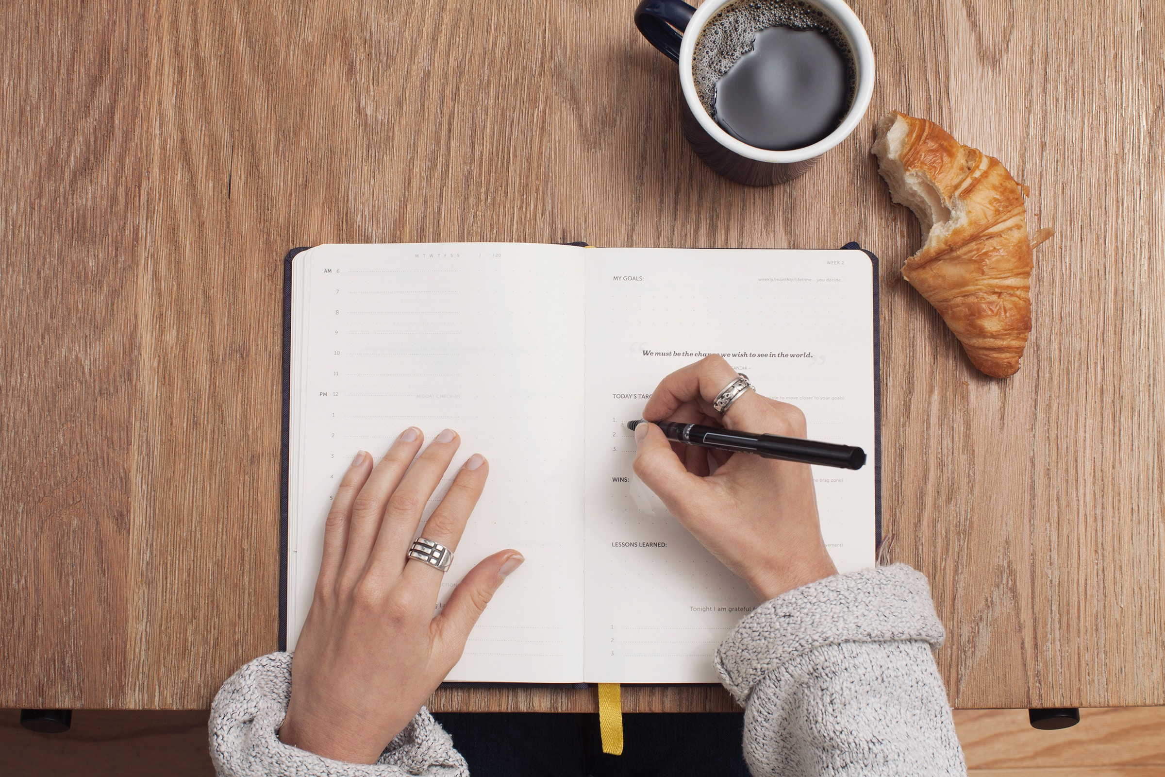 Image of coffee cup, croissant with a bite taken out of it, a planner, and a woman with a pen beginning to write in the planner.