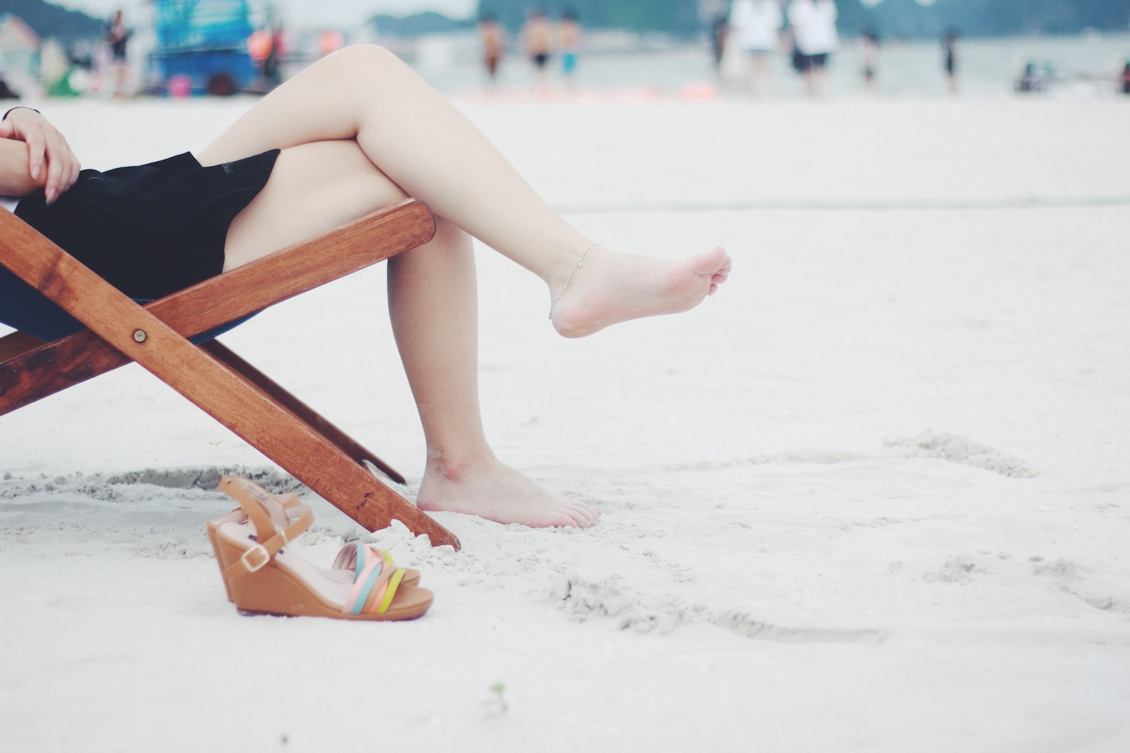 Woman sitting in foldable chair on the beach with her legs crossed
