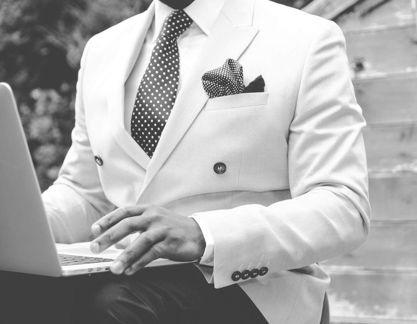 Black and white picture of a man in a suit sitting outside working on a laptop