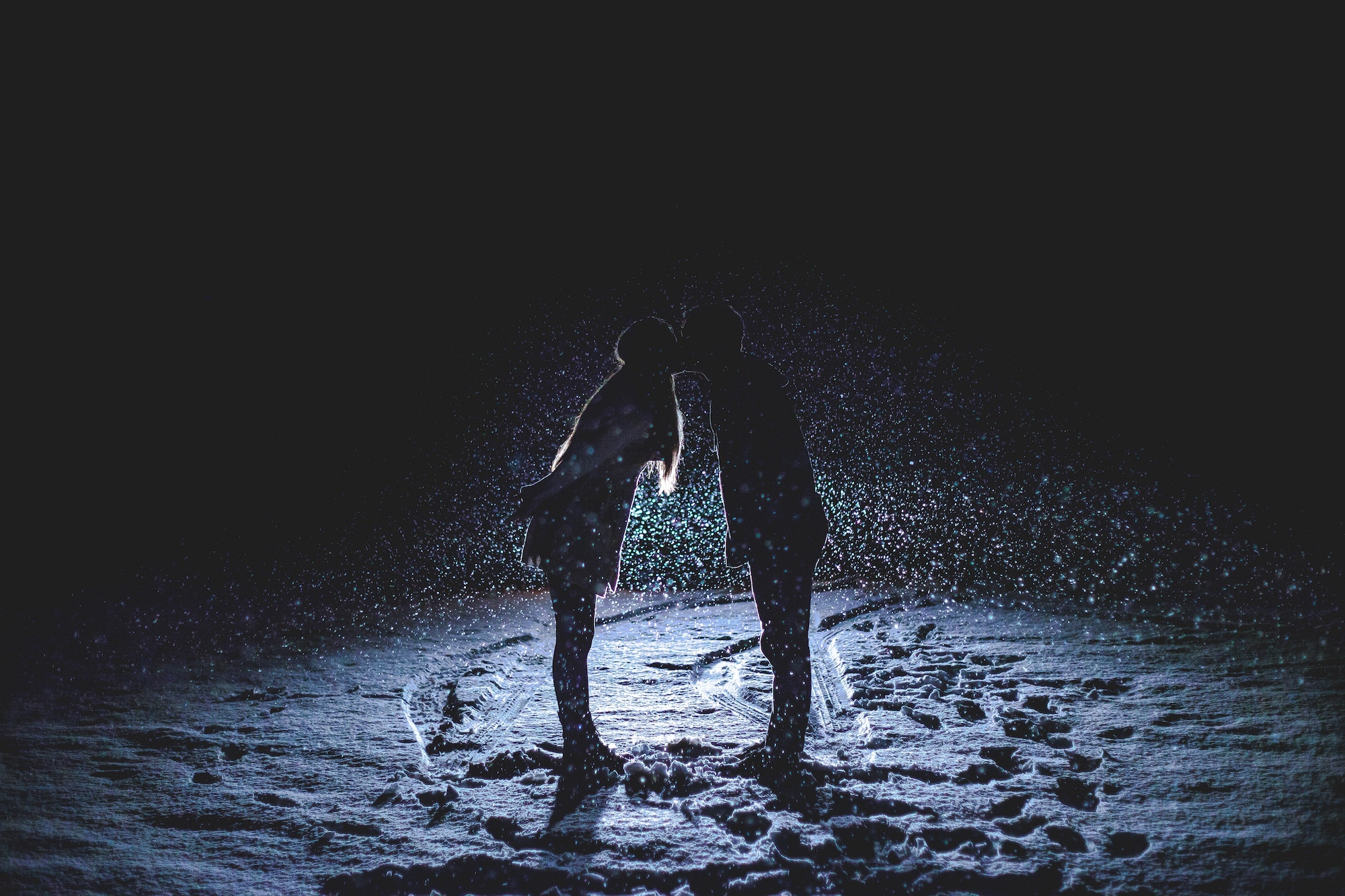 Two lovers kissing on a dark beach.