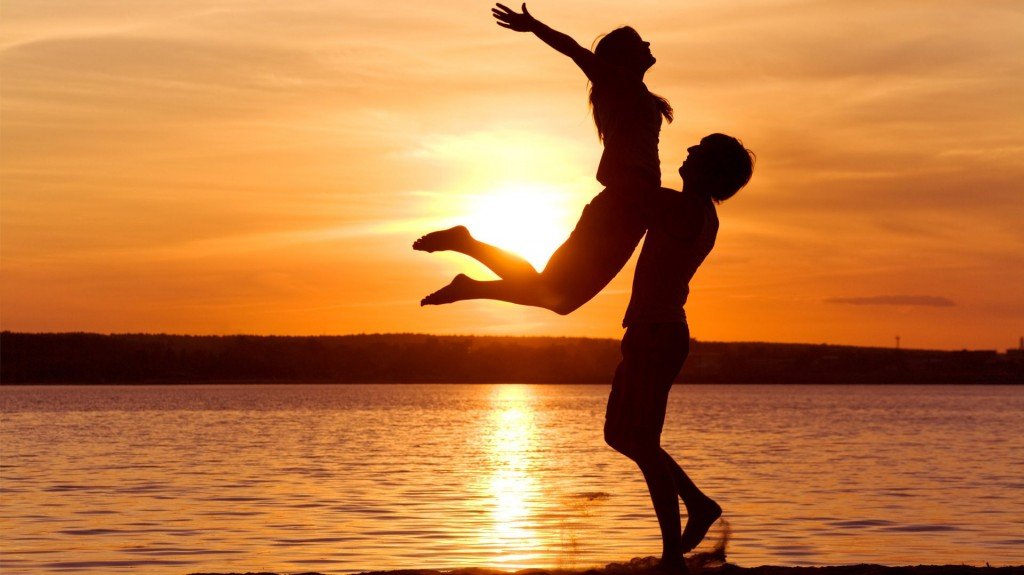 Silhouette of a woman jumping into man's arms in front of an ocean sunset