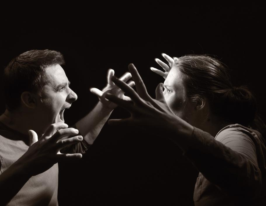 Black and white photo depicting an angry couple yelling with their hands raised