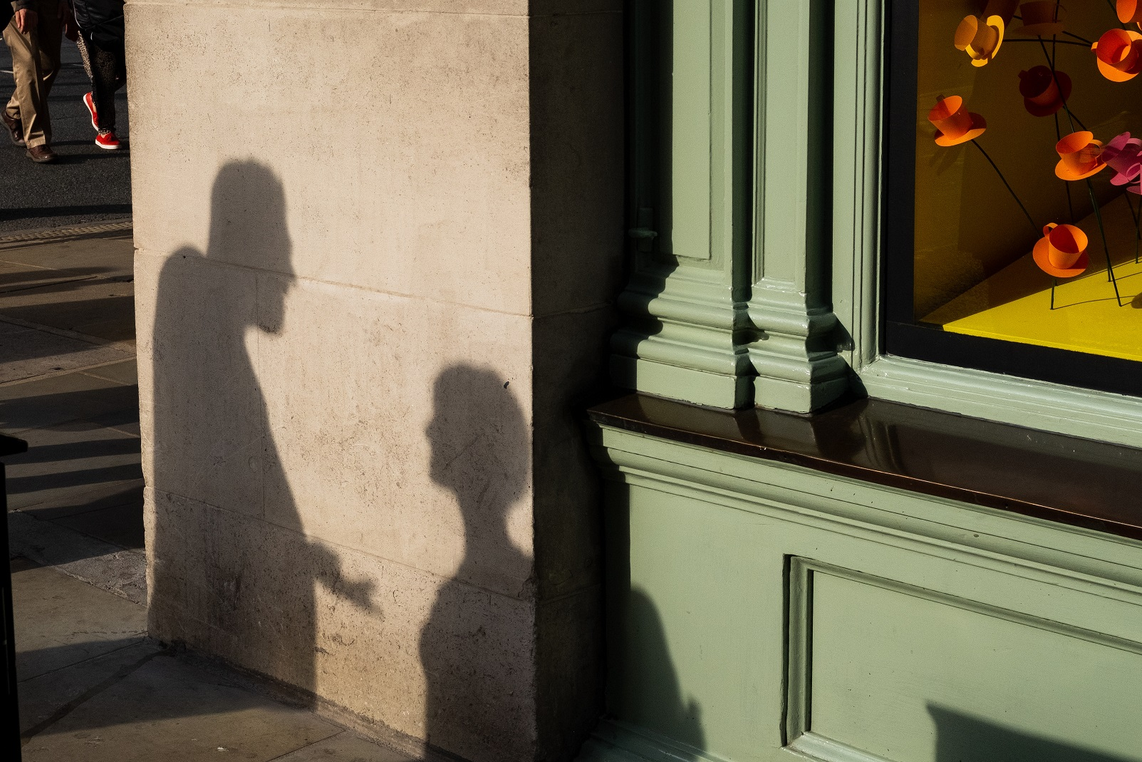 Shadow on side of building of man and woman having an unpleasant conversation.