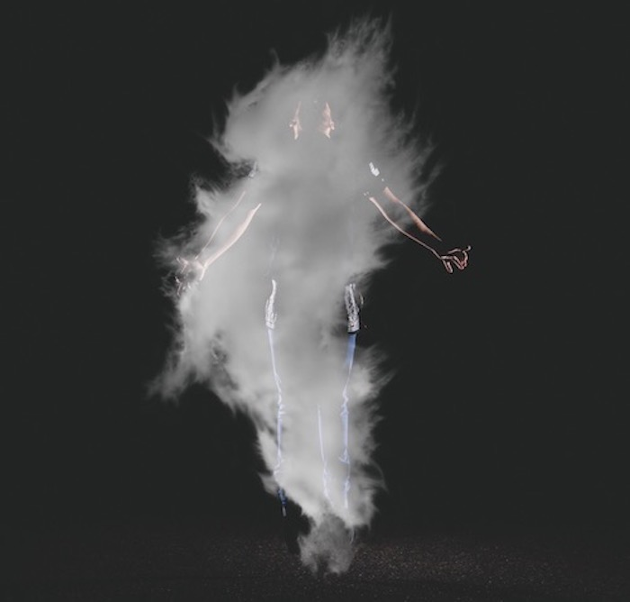 Cloud of white smoke in front of a man floating.
