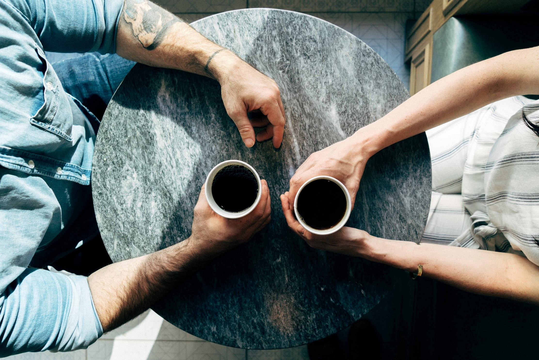 Above shot of woman and man holding coffee cups at a small marble table in a cafe