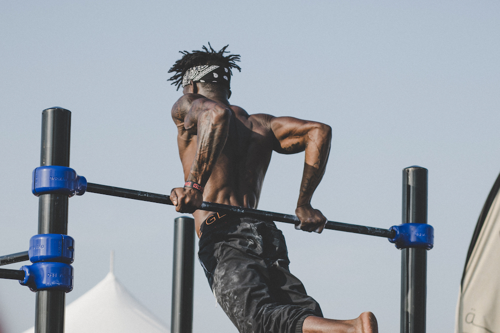Shirtless African American man doing reverse pull-ups.