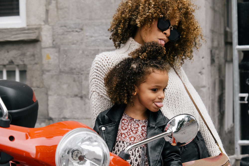 African American mother and daughter sticking their tongue out at the mirror on a motorcycle