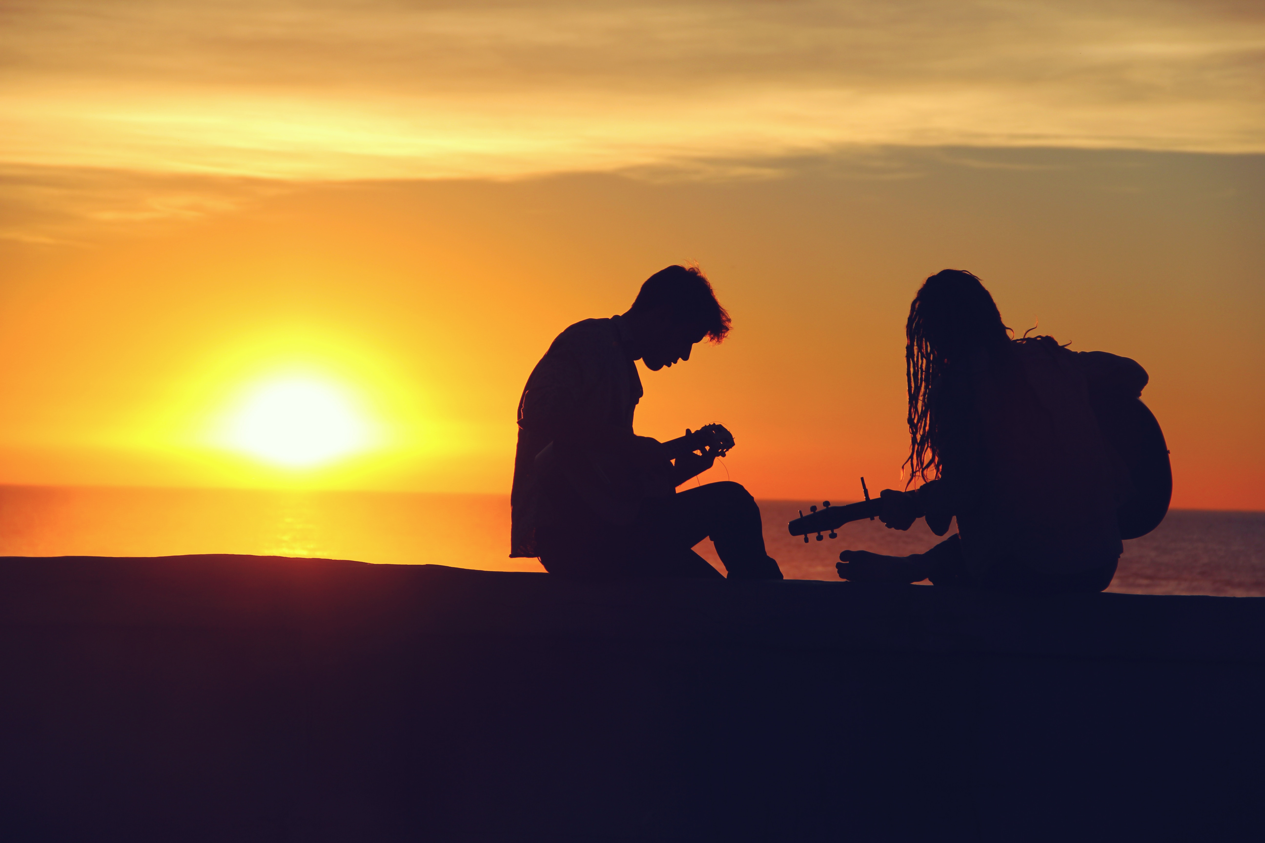 Young couple playing guitar in sunset