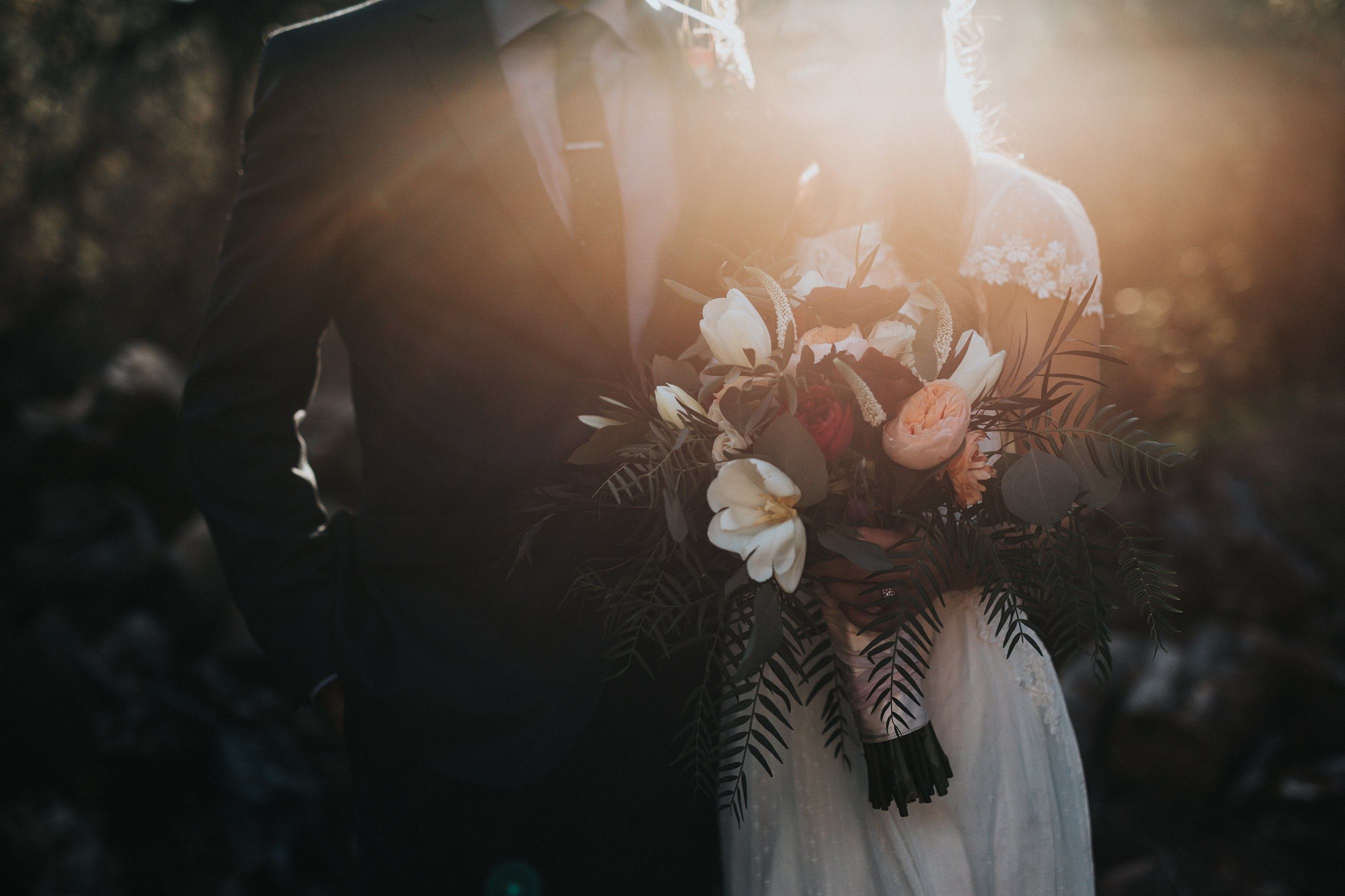 Slightly darkened image of a man in a tux and woman in a wedding dress holding a bouquet of flowers shot from the shoulders down.