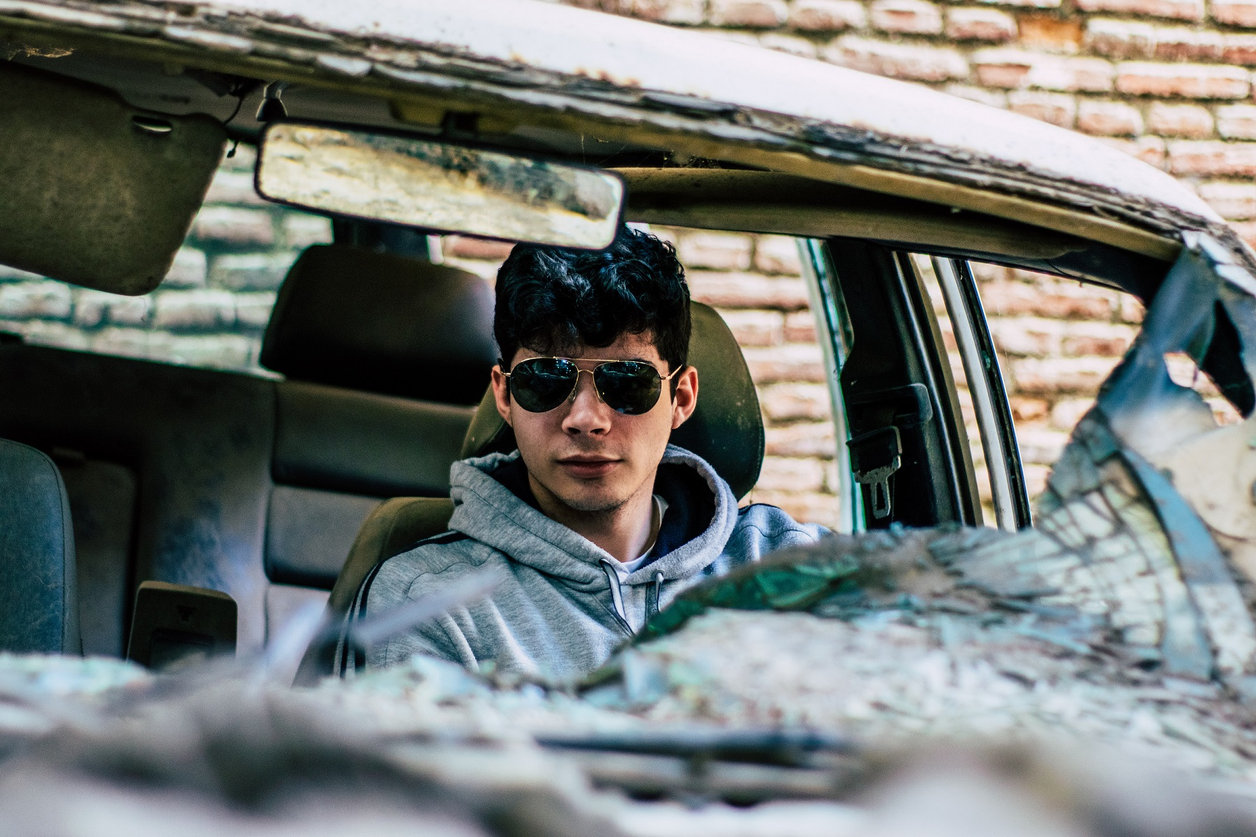 Boy in car with a smashed windshield and ruined interior fabric