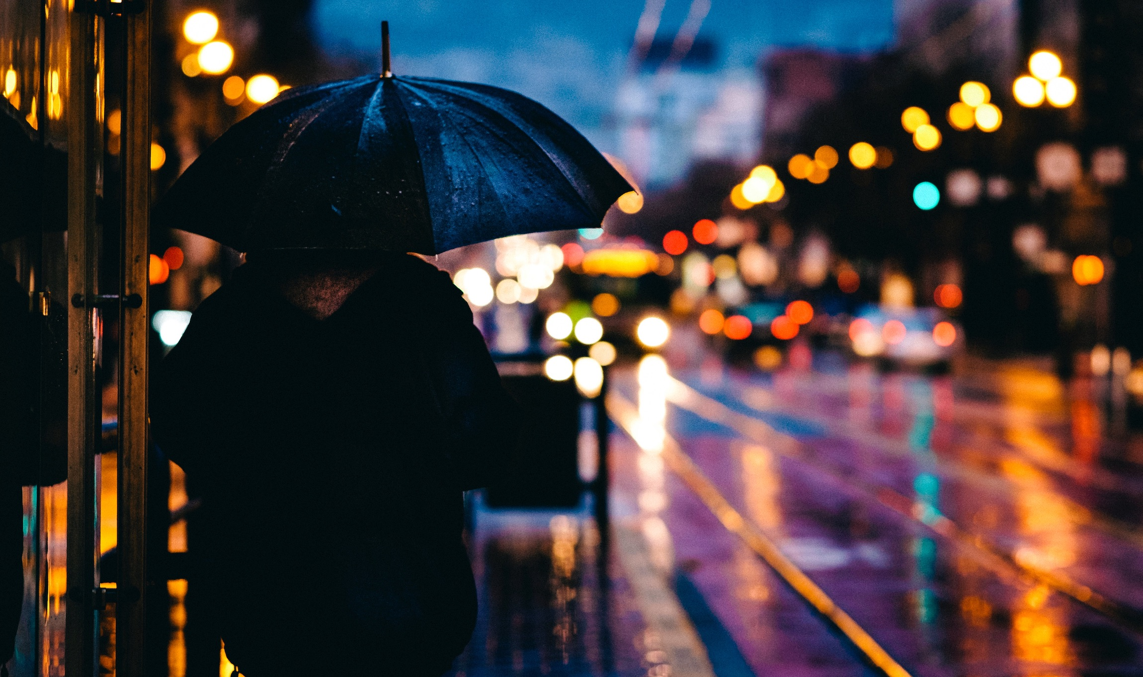 Cloaked man under an umbrella on a sidewalk near bright lights