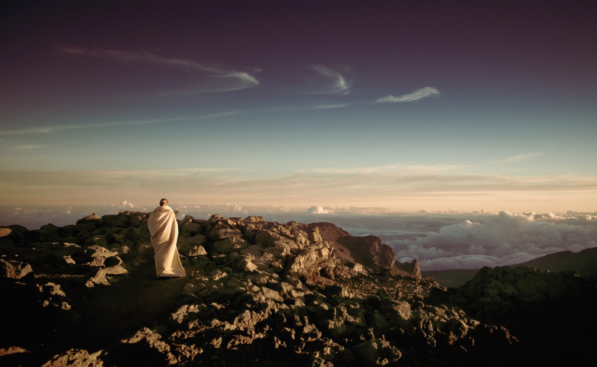 Monk in white wrap on top of a mountain, overlooking the clouds.