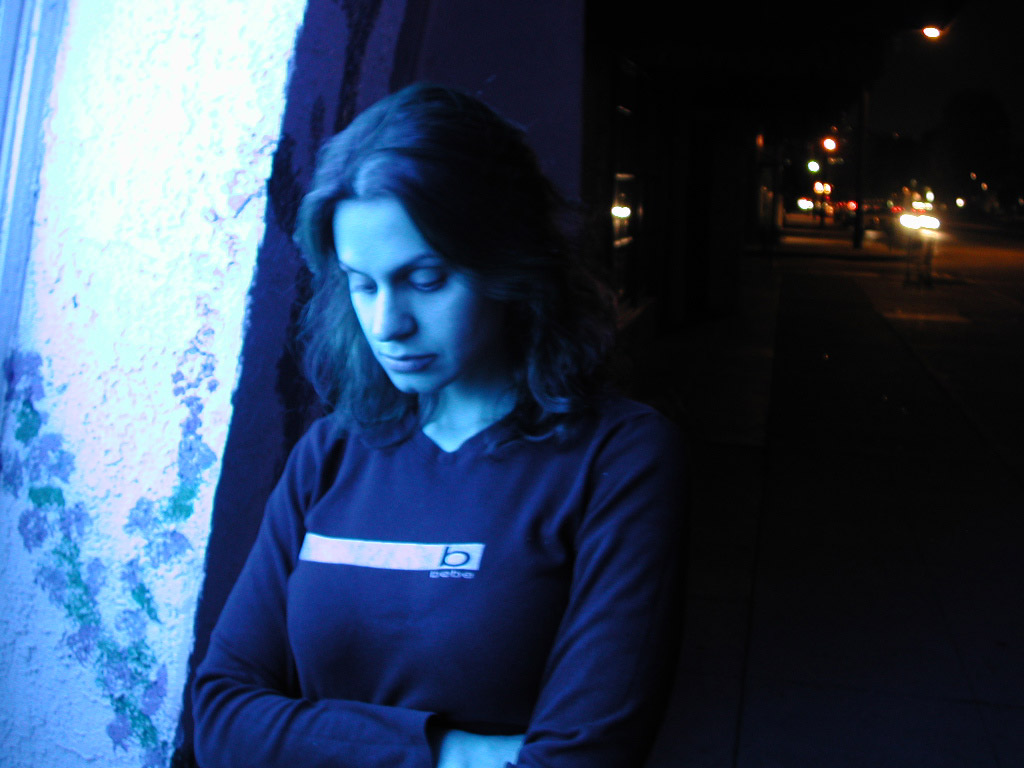 Woman leaning against a wall next to a window with her arms crossed and eyes looking downward.