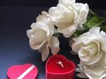 Four white roses surrounding a small red heart full of chocolates.