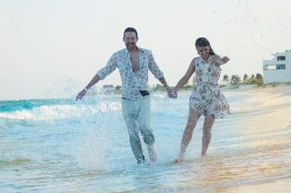 happy couple running together on beach