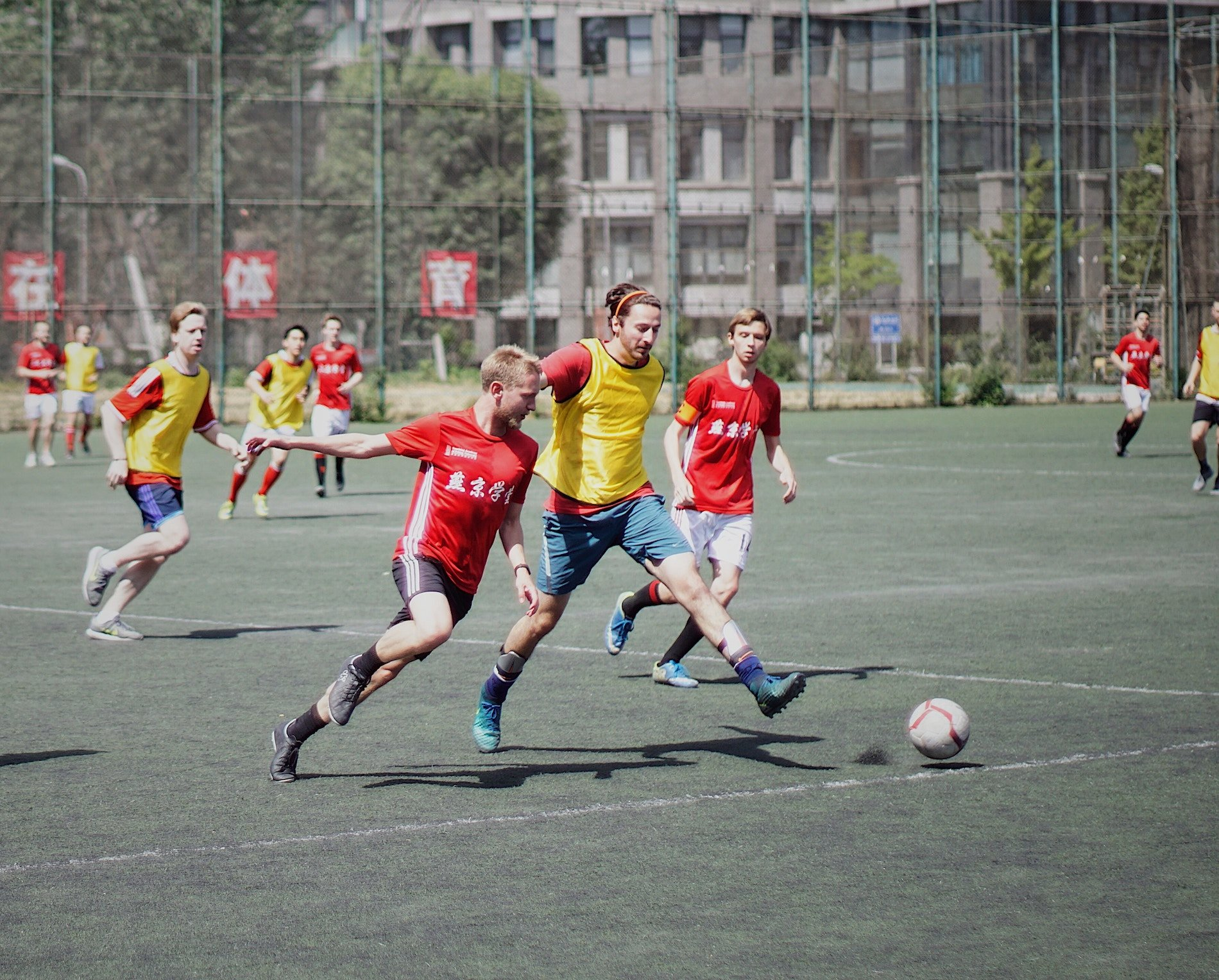 Three men- two of which are in red, the other in yellow - wearing soccer clothing with Chinese or Japanese kanji on it.