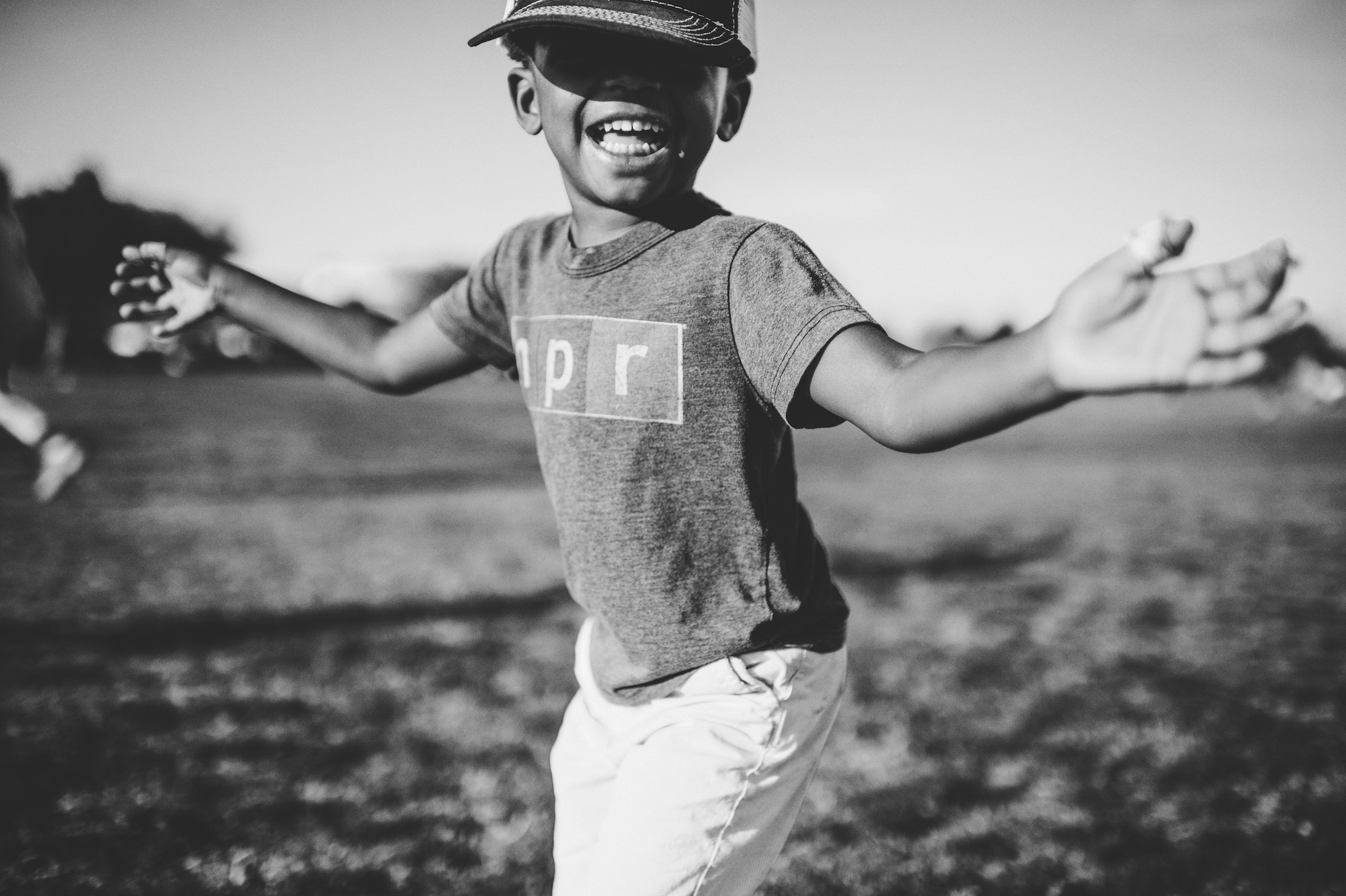 African American child with a baseball helmet on and his arms extended with a smile on his face.