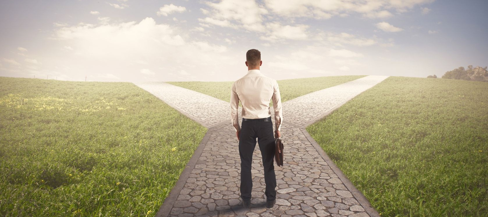 Man in a business suit standing at a literal crossroads