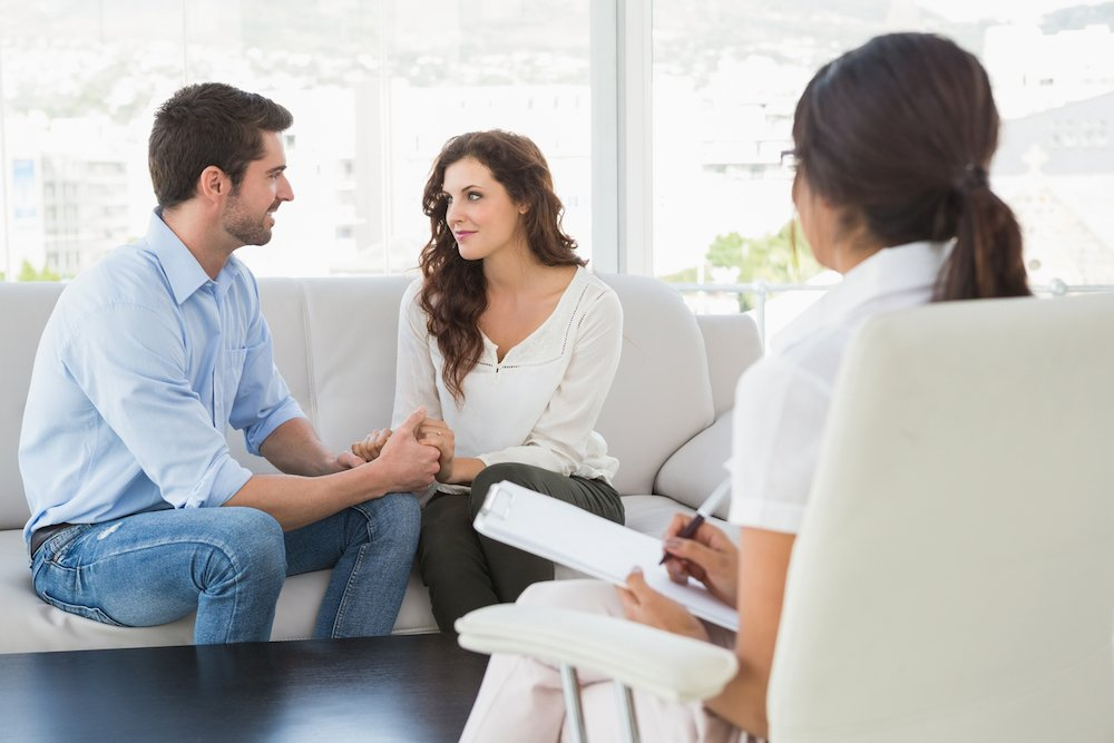 Man and woman talking and holding hands in a therapy session