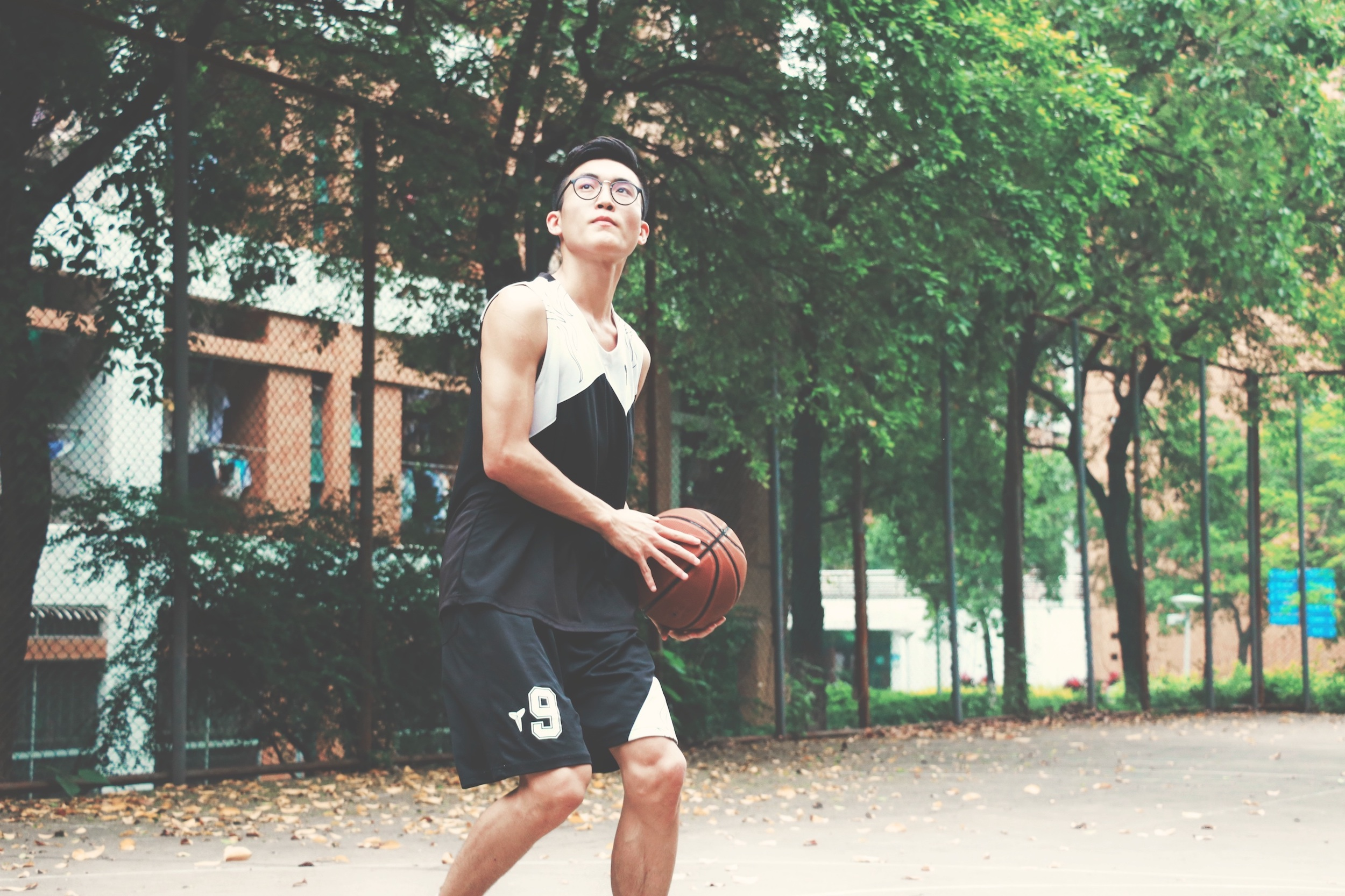 Young Asian male playing basketball.