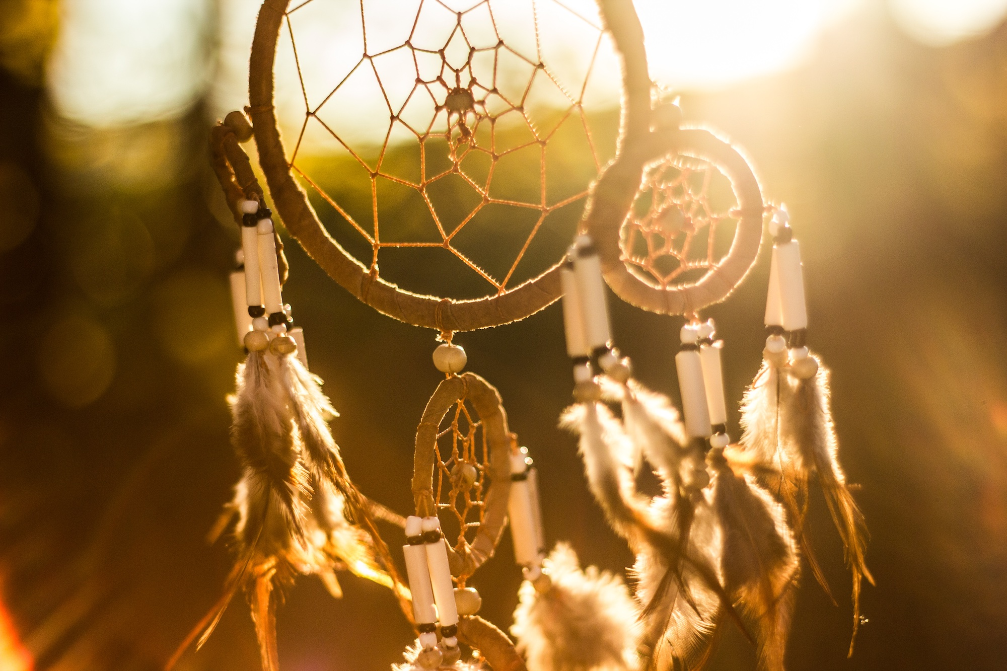 Dreamcatcher hanging outside in front of a bright sunset.