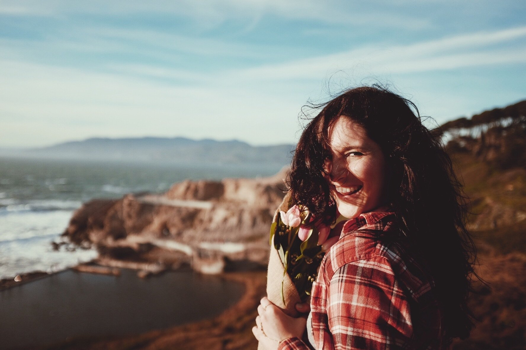 Smiling woman in a red flannel standing on the beach, the camera focused on her face and the flowers she's holding close to her face.