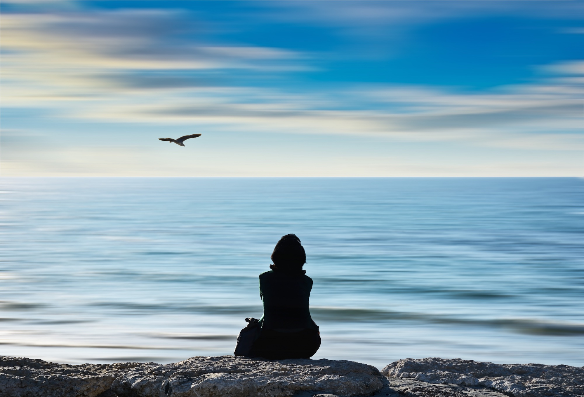 A woman meditating on the beach with seagull