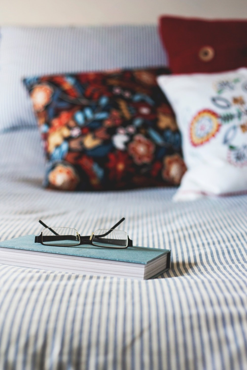 Black glasses on top of a light-turquoise journal sitting on a bed with faded blue stipes.