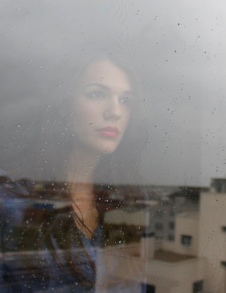 Reflective Woman Looking Out Window