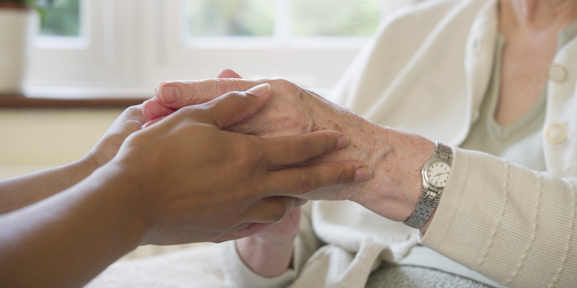 Young caregiver embracing the hands of an elderly woman