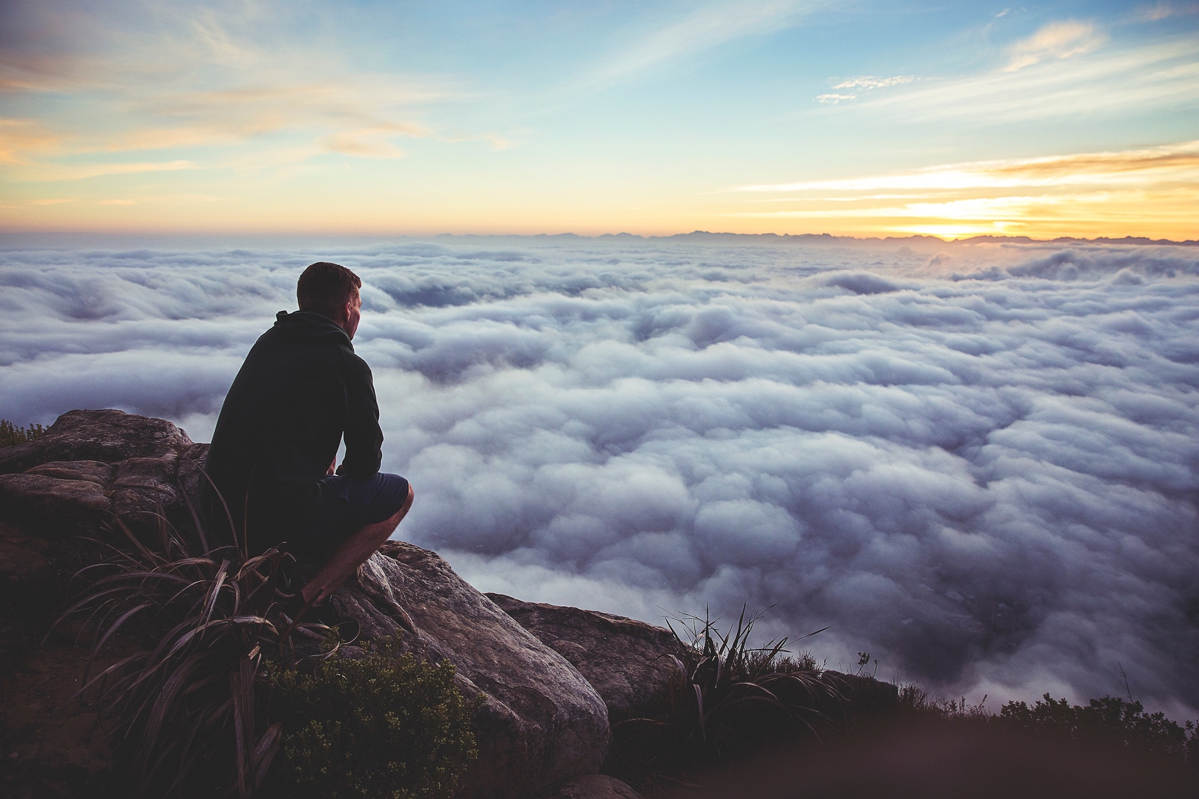 A man looking into the clouds on top of a mountain