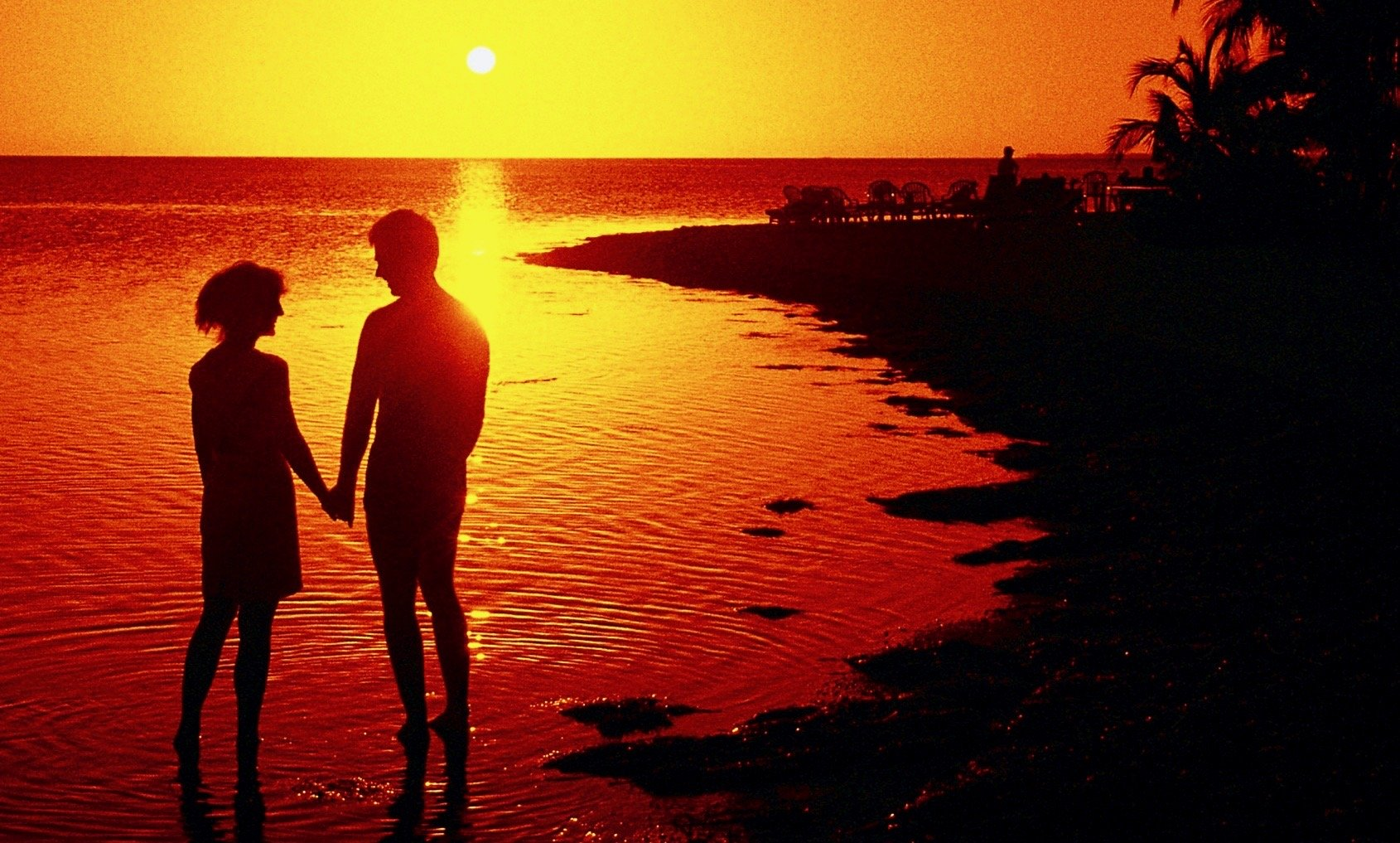 Silhouette of a man and woman holding hands on the beach at sunset