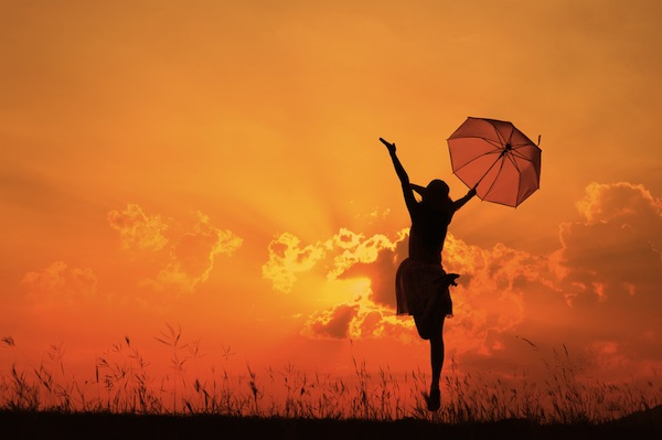 Silhouette of a woman in a dress holding an umbrella jumping